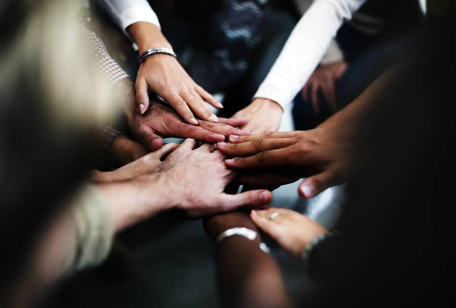 A photo of many hands put into a circle in a show of team unity.