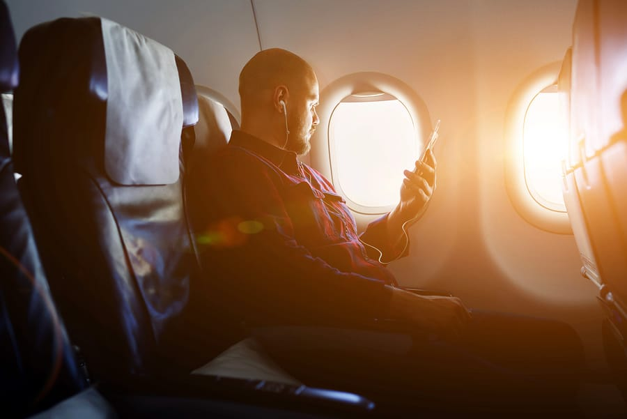 A photo of a man sitting on a plane, listening to something on his phone through earbuds.
