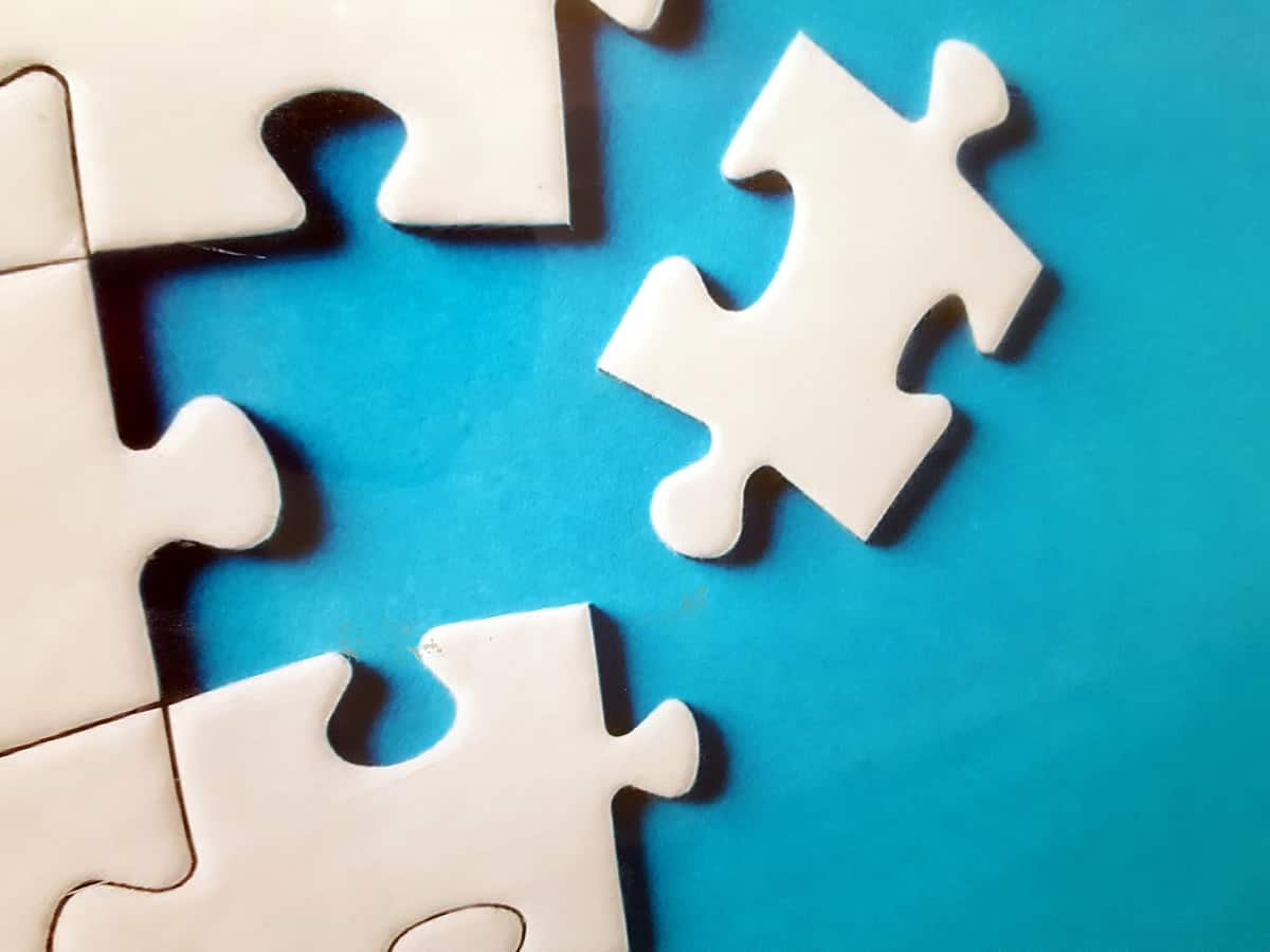 A close-up photo of five puzzle pieces together and one ready to be placed.
