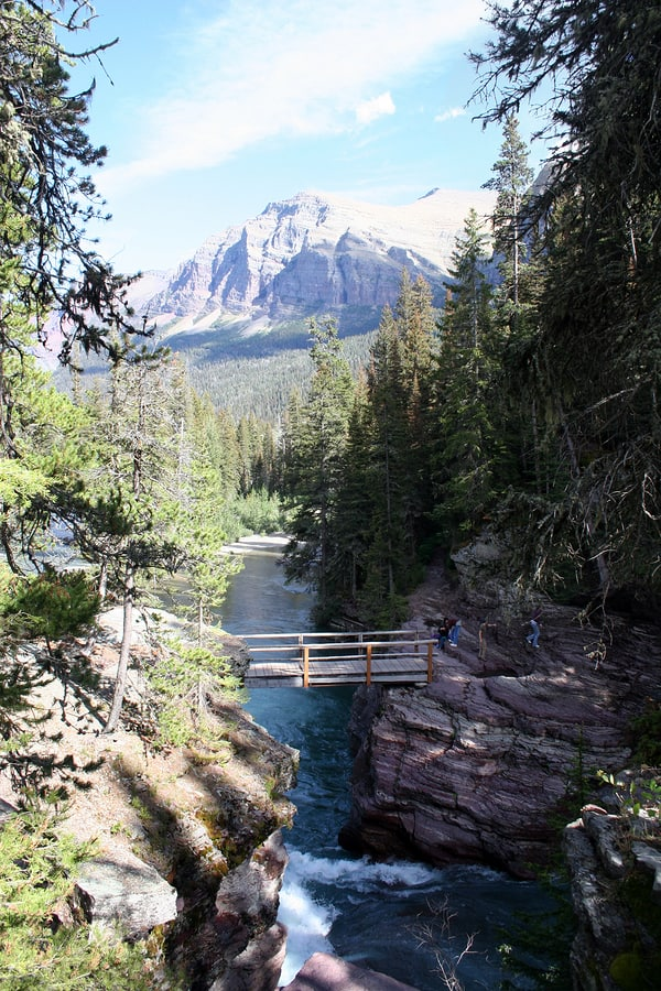 A photo of St. Mary's Falls in Glacier National Park with giant mountains in the background.