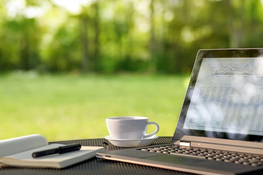 A photo of a laptop, paper notebook, and cup of coffee sitting on a table outside.