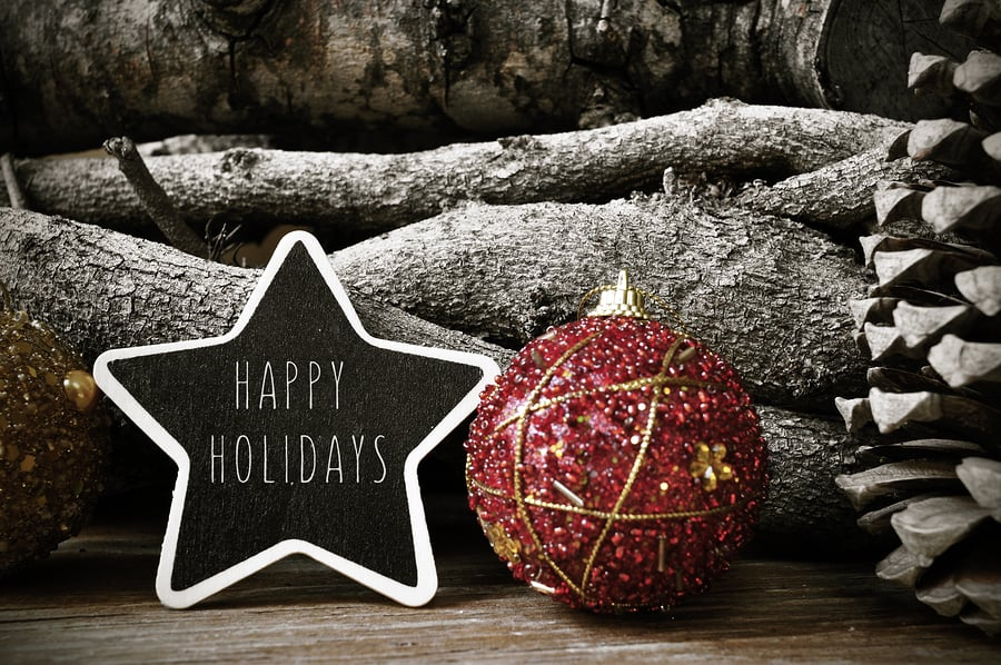 "A photo of rustic holiday decorations and a star-shaped sign reading ""Happy Holidays."""