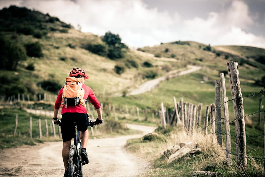 A photo of a man in a red helmet and jacket riding a bicycle down a trail. In visual design, color can be used to highlight new or important elements.