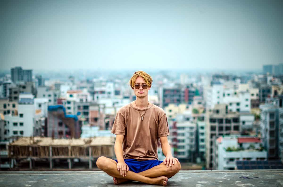 Image of a man meditating on top of building with a city surrounding him.