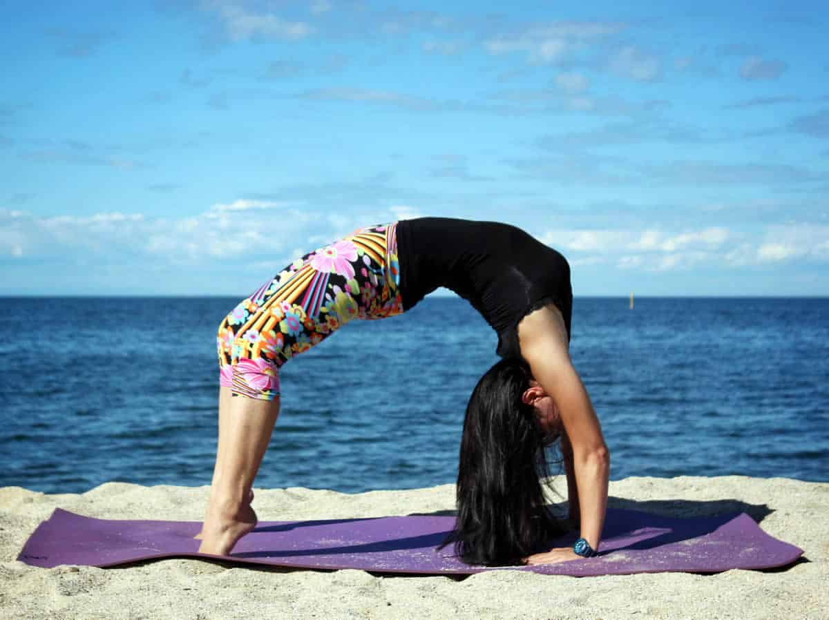 A photo of a woman doing yoga on a beach.