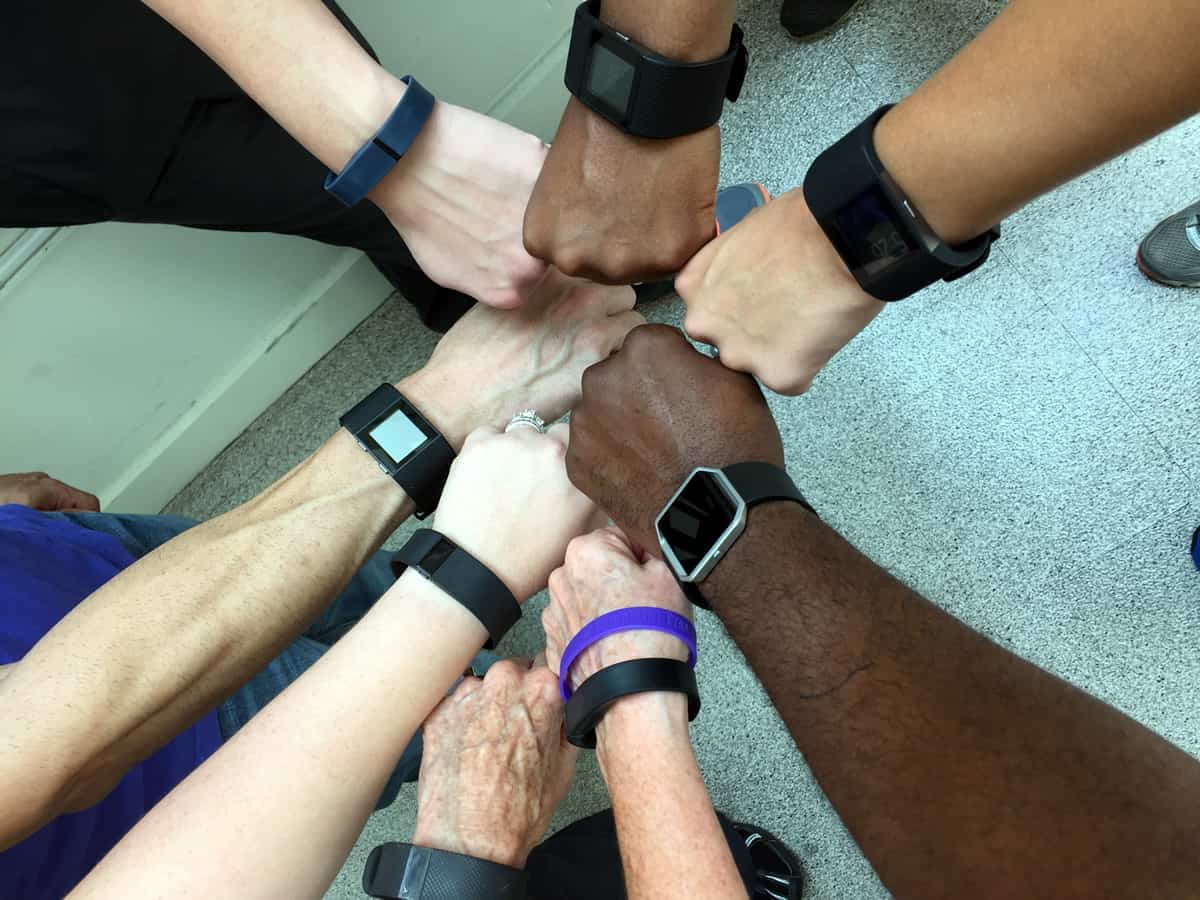 A photo of people putting their fists together in a circle, showing off their various Fitbit wearables.