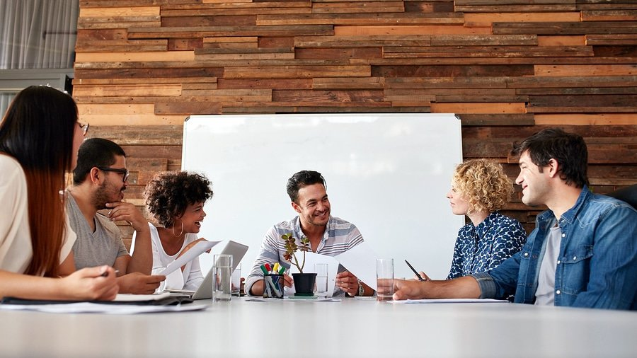 A photo of a team of happy people in a meeting.
