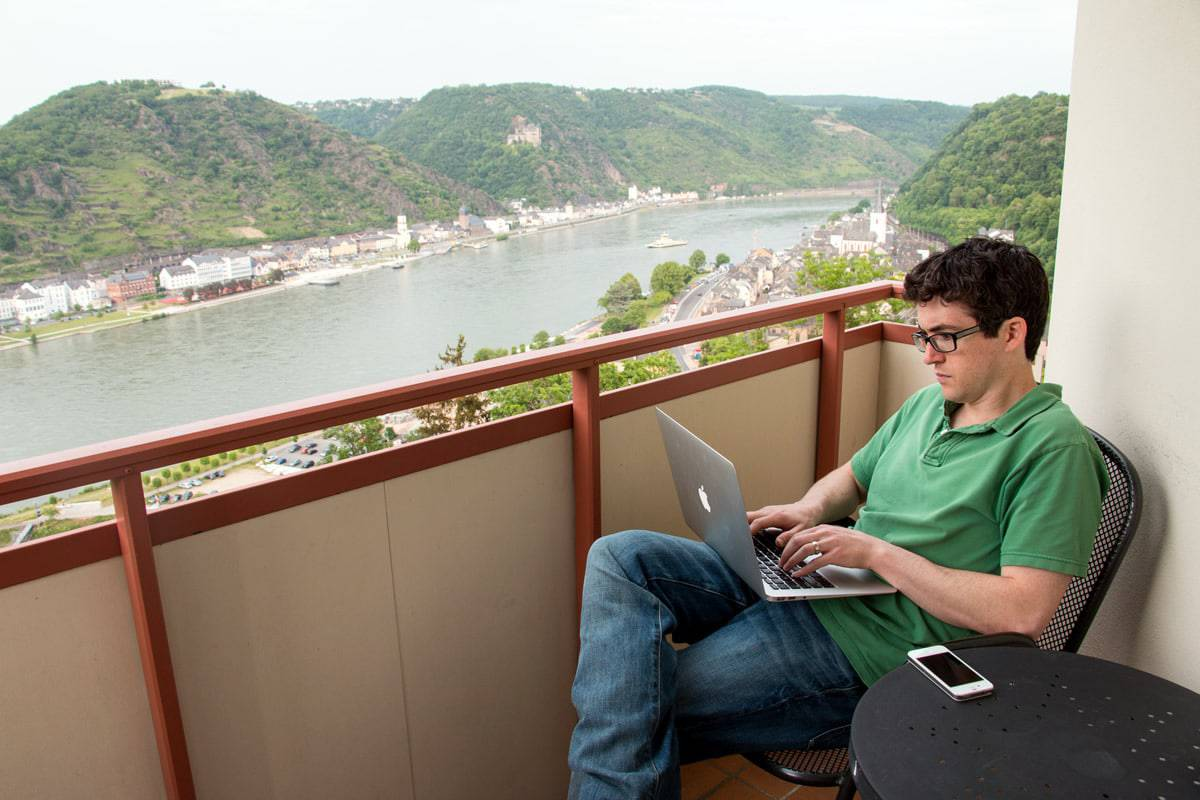 A photo of a man using a laptop while sitting on a balcony overlooking a river.