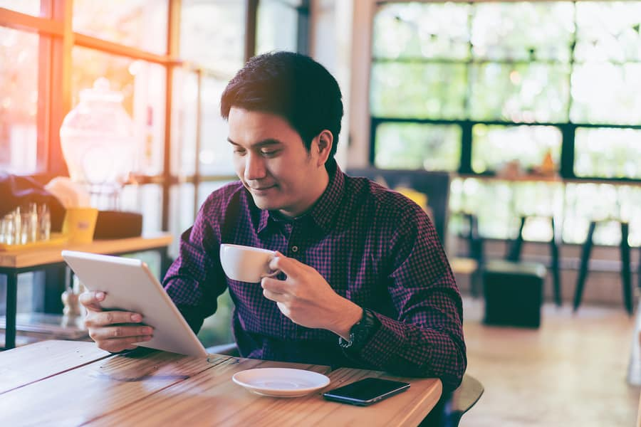 A photo of a man working on his tablet at a coffee house at sunset.