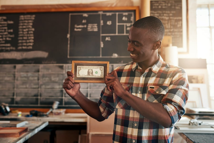 A photo of a man holding up the first dollar he made in a picture frame.