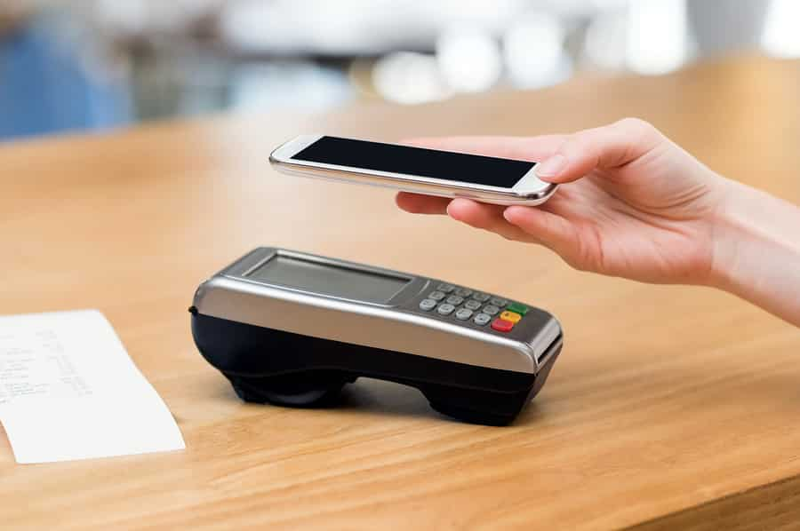 A photo of a person holding their phone above a credit card terminal while using the mobile pay feature.