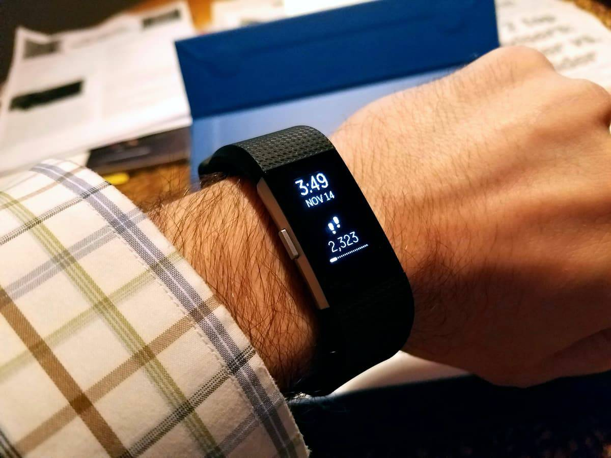 A photo of a man checking his step count on a Fitbit Charge 2 during the workday.