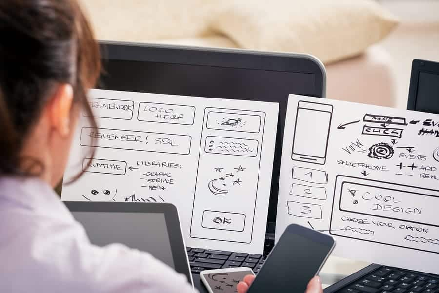 A photo of a designer studying sketches of her latest mobile app design.