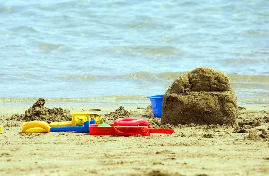 A photo of an unfinished sand castle surrounded by plastic tools and buckets.