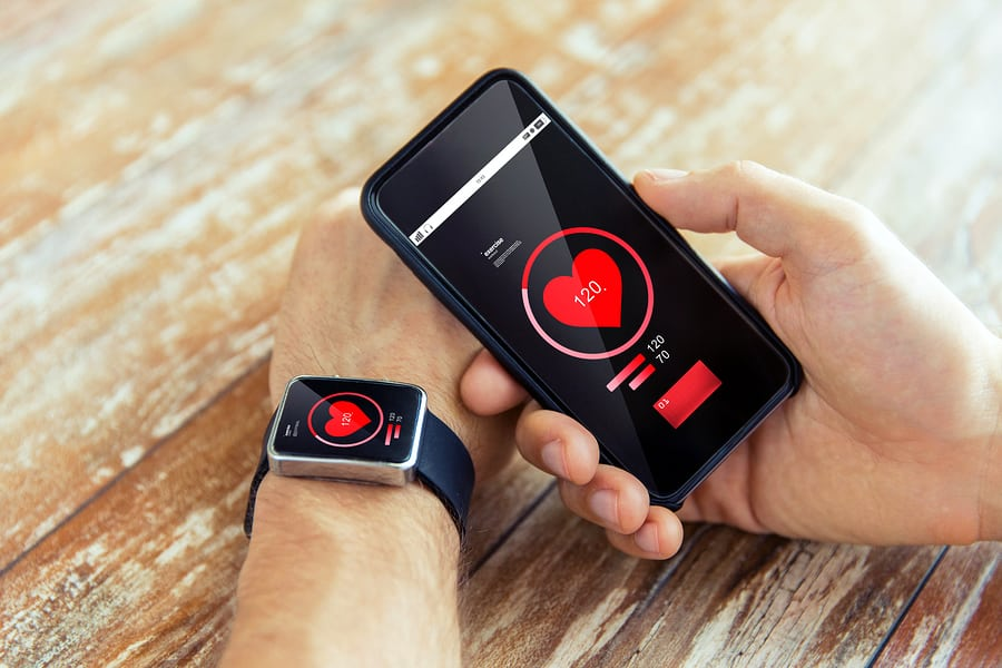 A photo of someone syncing their smartwatch to an app on their smartphone.