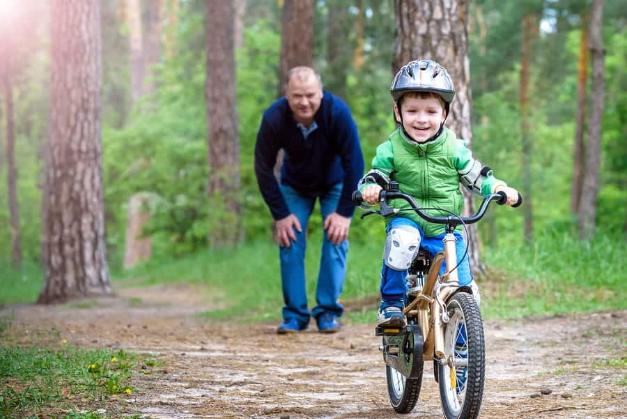A photo of a dad helping his child learn how to ride a bike without training wheels.