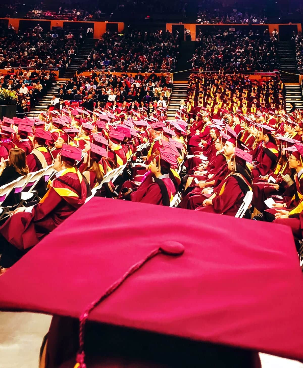 A photo of graduates in their red caps and gowns at a commencement ceremony.
