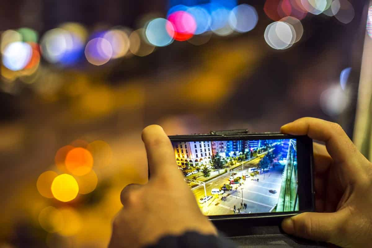 A photo of a person taking a picture with his smartphone of a brightly lit street at night.