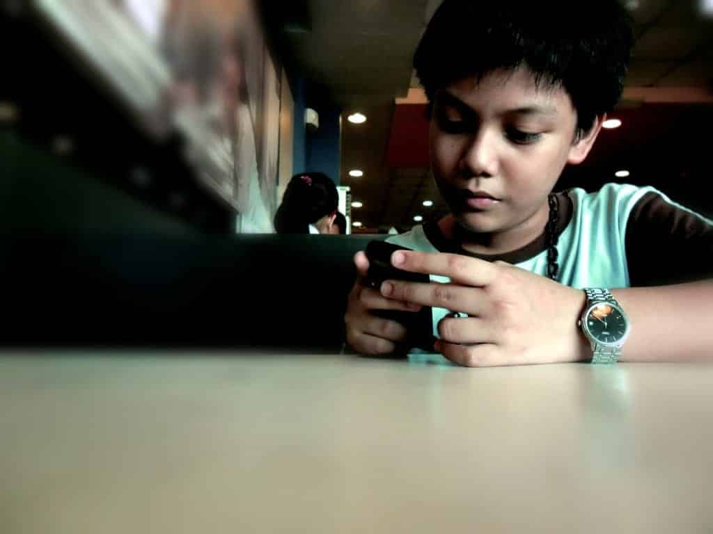 A boy browses the Internet on his phone.