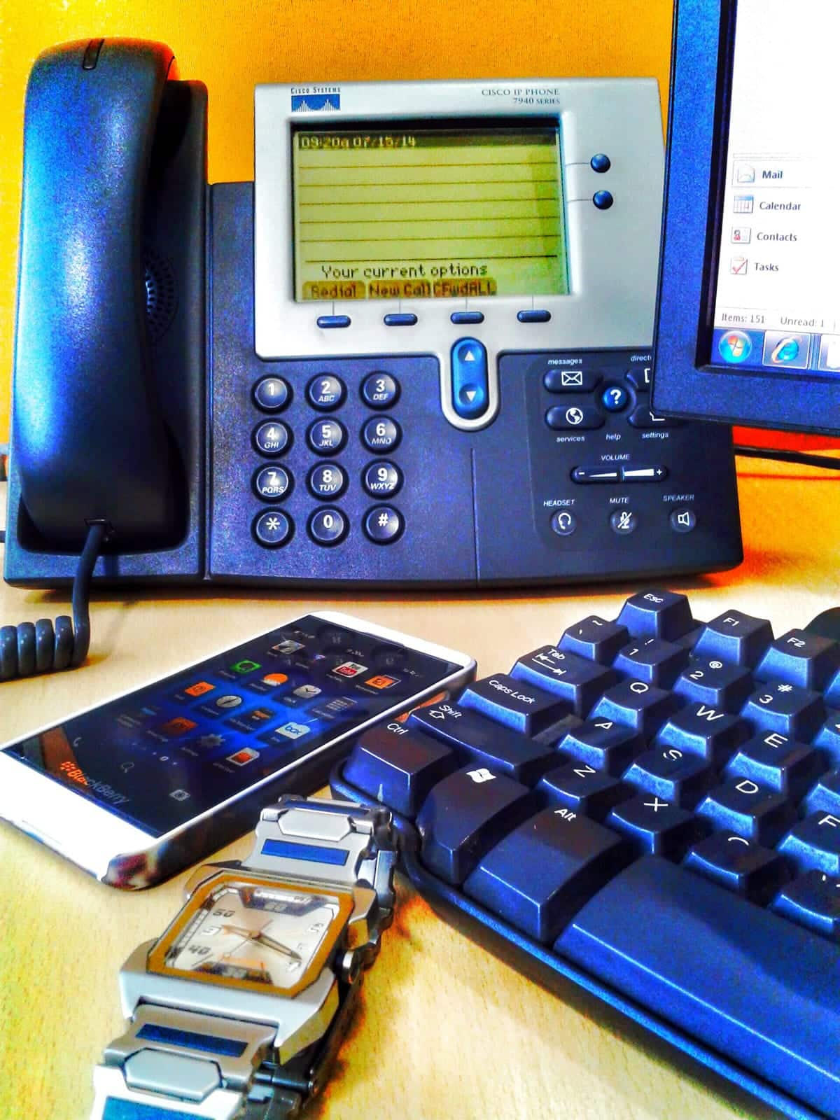 A smartphone, watch, computer and office phone on a desk.