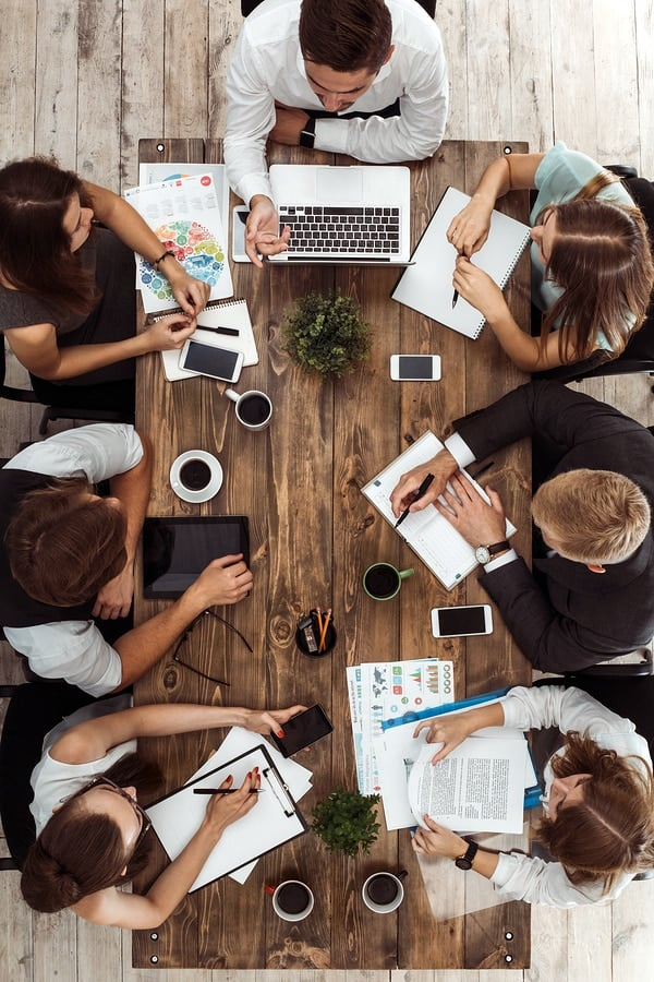 A top-down view of a development team sitting around a wood table for a meeting.
