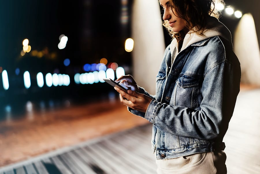 A photo of a woman checking her smartphone at night on the boardwalk.