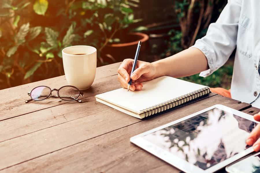 A photo of a designer sketching in a notebook outside with morning coffee.