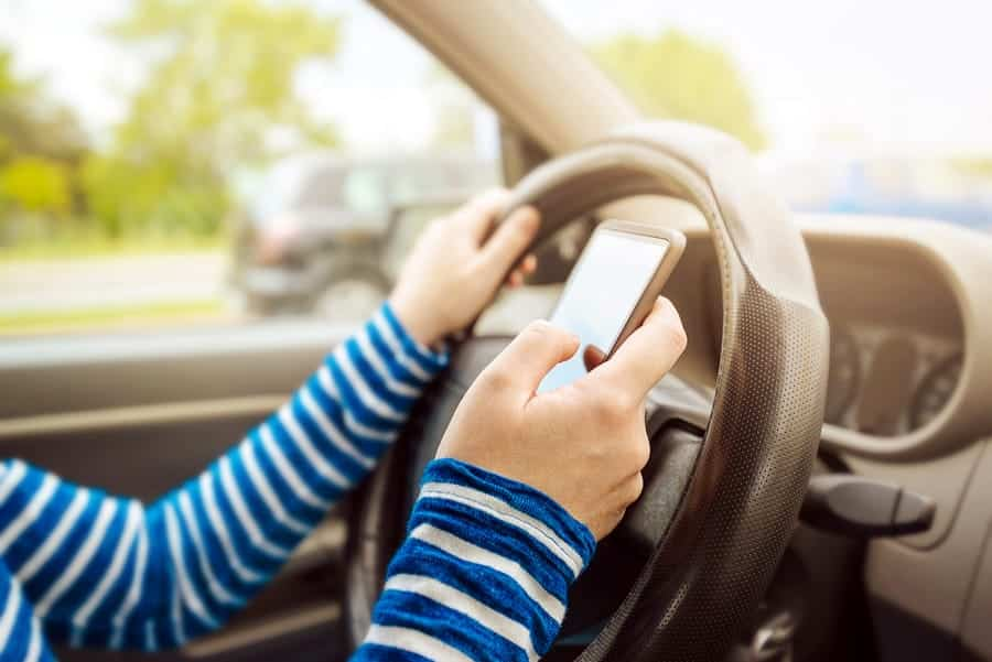 A photo of a person texting while driving.