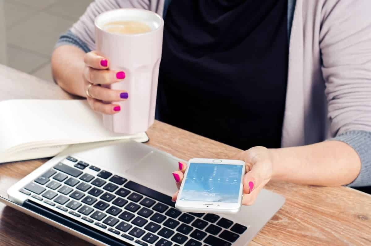An image of a woman holding her phone and a coffee drink.