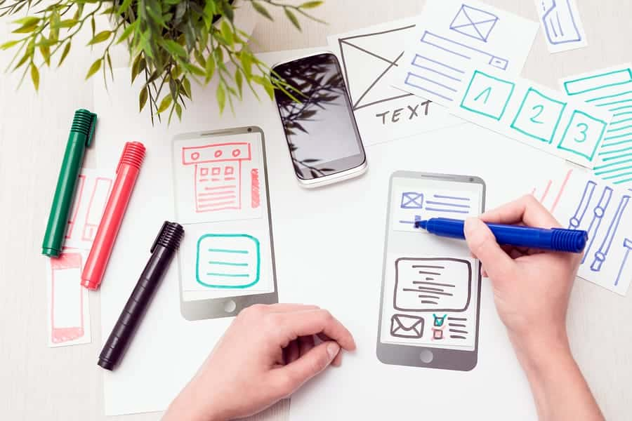 A photo of a person drawing color coded wireframes of a new mobile app design.