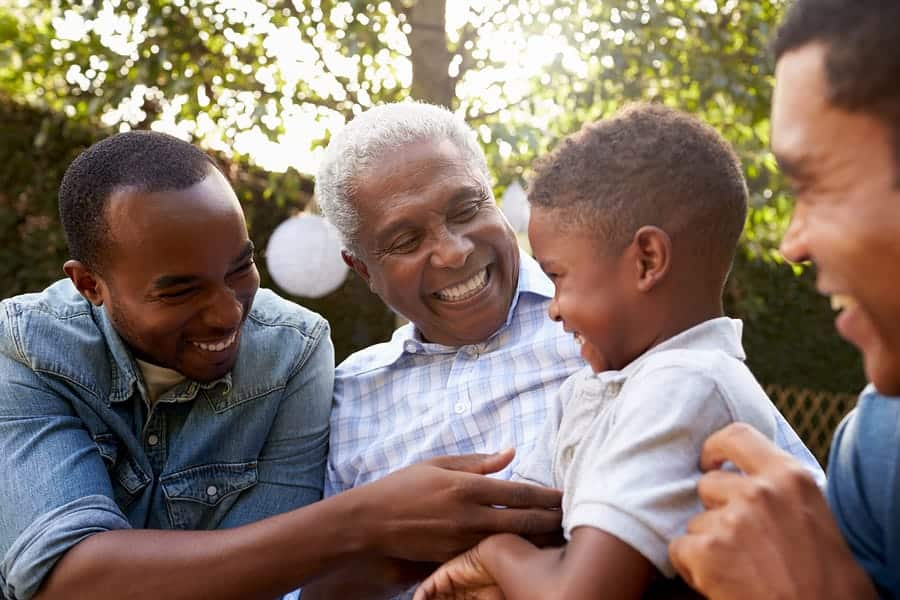 A photo of a grandfather laughing with his sons and grandson at a family gathering.