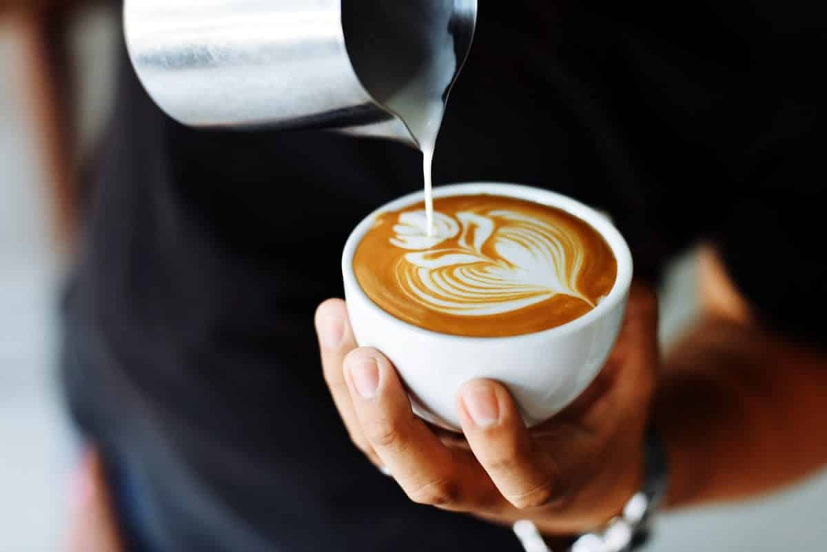 An image of a person making a latte at a cafe.