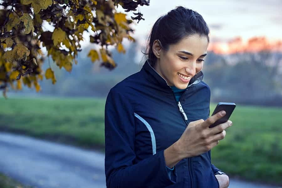 A photo of a woman taking a walk in the early morning, smiling at something on her smartphone.