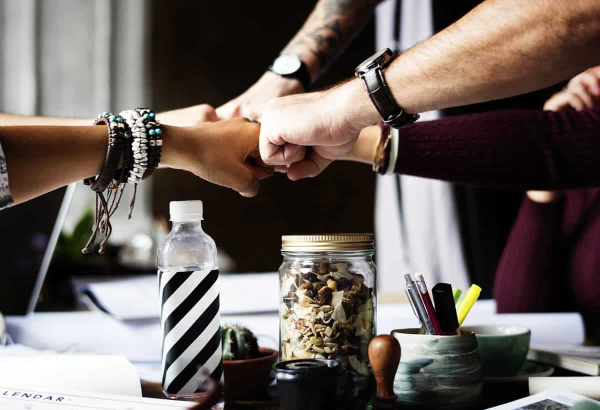 An image of a team fist-bumping in the middle of the table after a meeting.