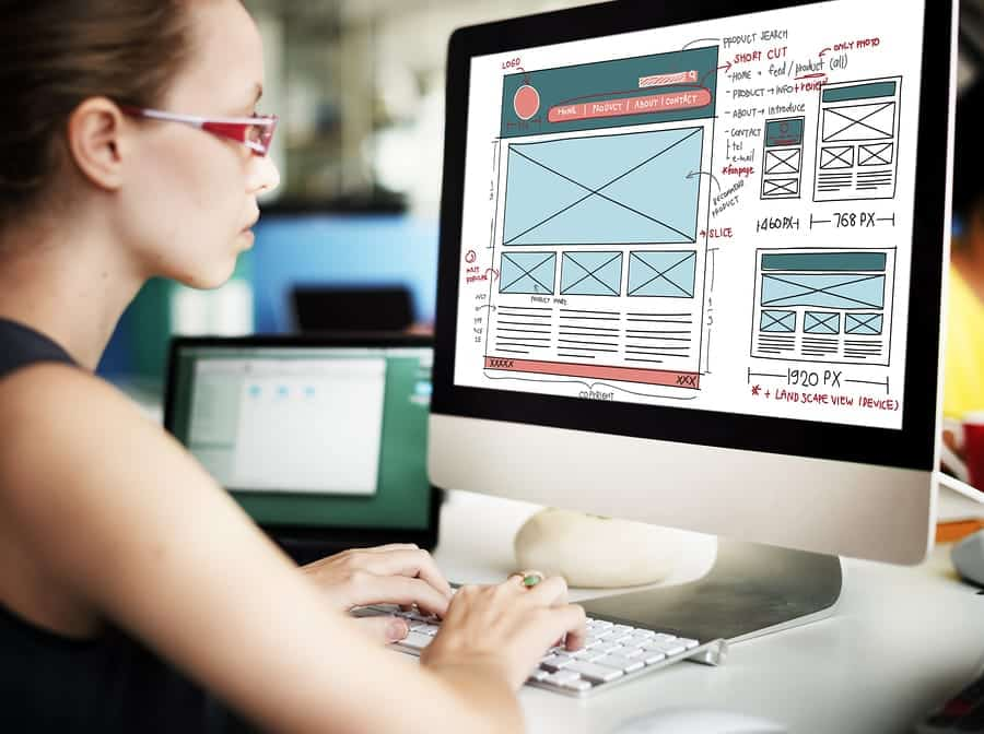 A photo of a web designer working on a website layout on her computer.