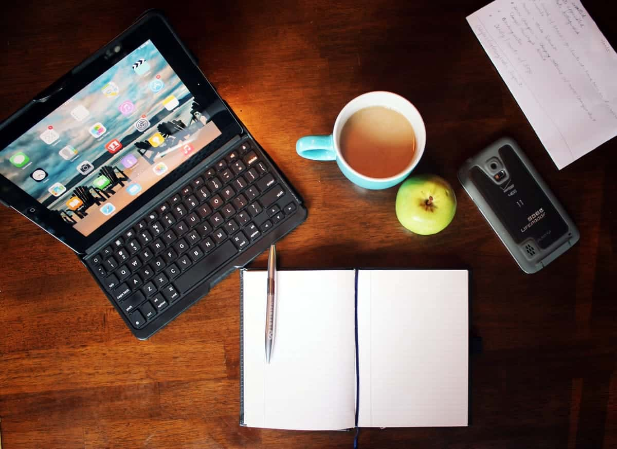 A top-down photo of someone's workspace, including a tablet, coffee, smartphone, and a notebook.