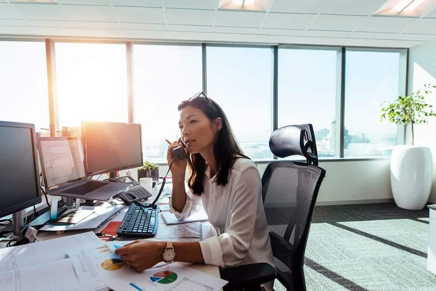 A photo of a woman taking on the phone in her brightly lit office.