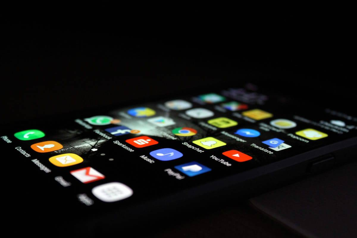 An image of a smartphone with a dark background and many apps downloaded on it.
