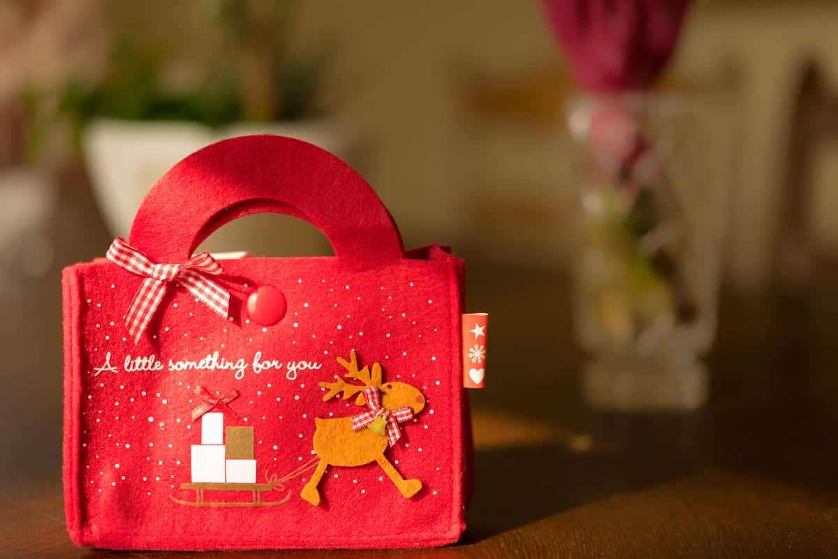 A photo of a red felt gift bag with a reindeer pulling a sledge full of presents.