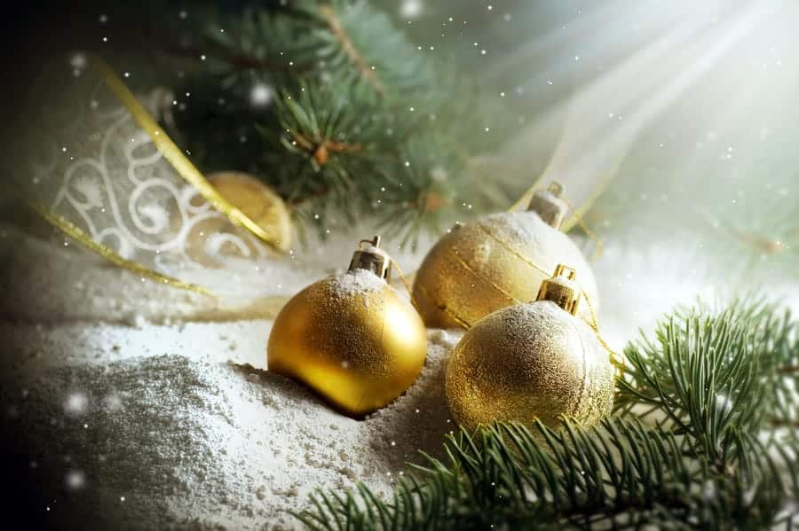 A photo of gold Christmas ornaments and pine tree sprigs sitting in the snow.