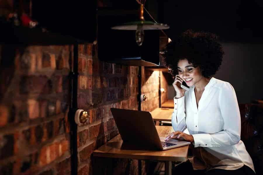 A photo of a woman taking a work call in the evening.