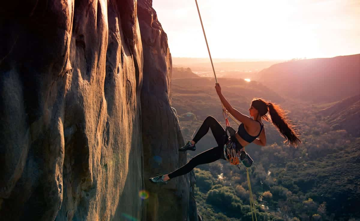 An image of a woman climbing a mountain using a rope.