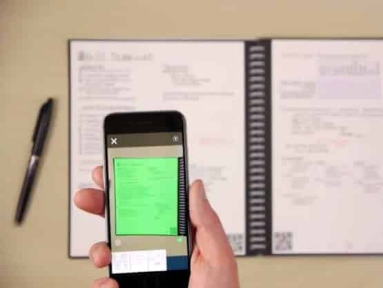 A photo of a person using their smartphone to take a photo of their Rocketbook to upload to the cloud.