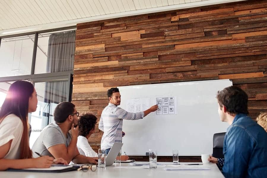 A photo of a man giving a presentation to his design team using a whiteboard.