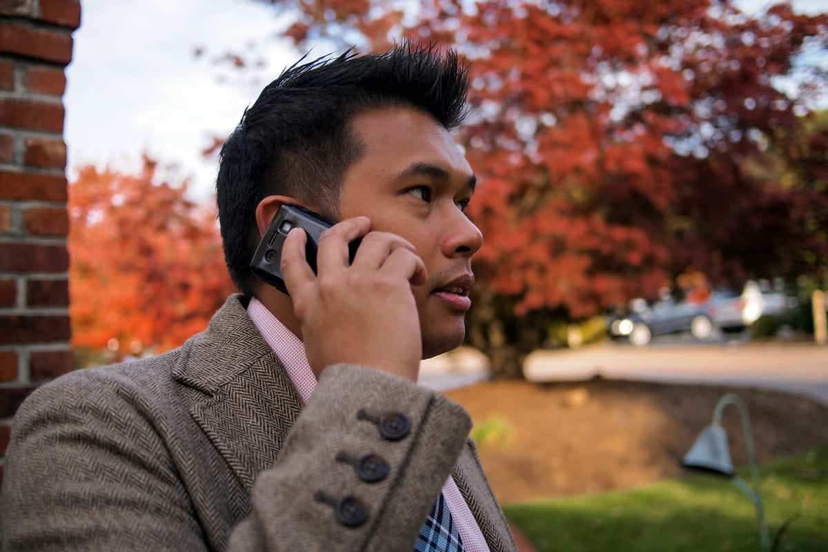 A photo of a man taking a business call on his cell phone outside on an autumn day.