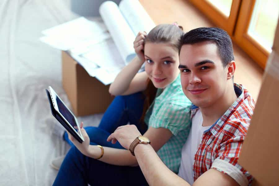 A photo of a couple using their tablet on moving day.
