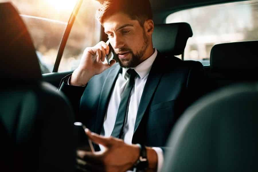 A photo of a man on a business call while riding in a car.