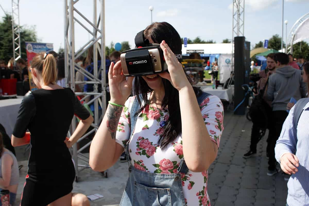 A photo of a woman wearing a VR headset outdoors at a festival.