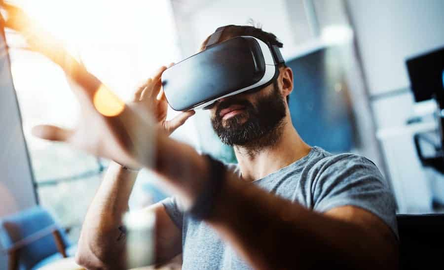 A photo of a man wearing a VR headset, reaching out for something in front of him.