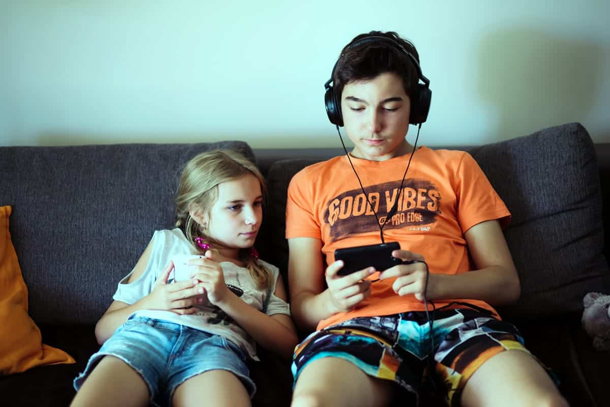 A photo of a brother and sister sitting on the couch, playing with their smartphones.